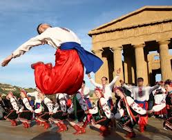 Folk groups from various parts of the world cheer and dance along to the tunes of their traditional melodies